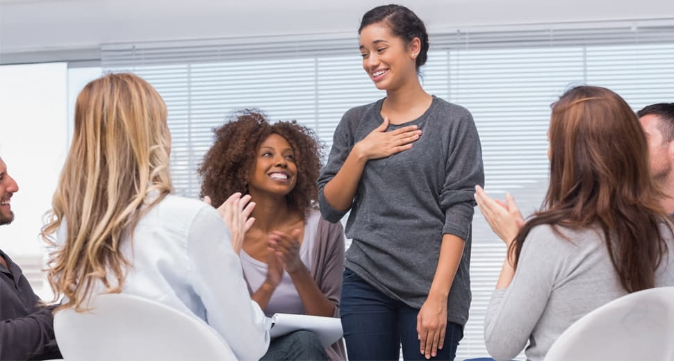 female standing and taking applause during a group therapy session